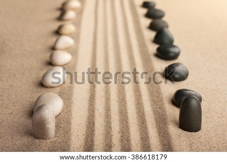 Stripe of white and black stones lying on the sand, can be used as a background - stock photo