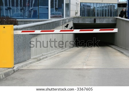 Striped automatic barrier partitioning off entrance to a tunnel to city in the summer