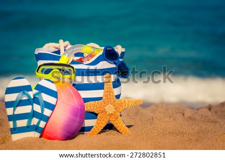 Striped bag, starfish and flip-flops on the beach. Summer vacation concept