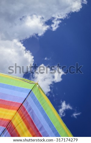 Striped beach umbrella underside, blue sky and white clouds seen from under  point of view