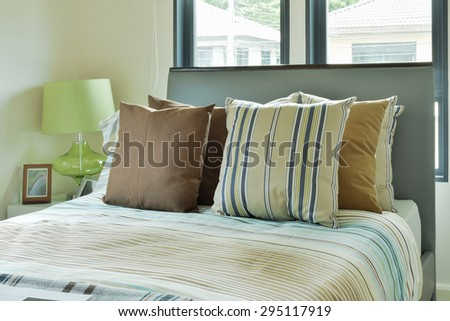 Striped bedding in modern decorated bedroom - stock photo