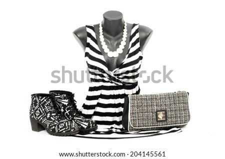 Striped blouse on mannequin with matching accessories. Black and white blouse on tailor's dummy with matching purse and shoes. - stock photo