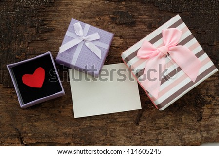 Striped box and opened purple box with red love symbol inside purple box and a piece of paper on old wooden table. Vintage look. Conceptual.