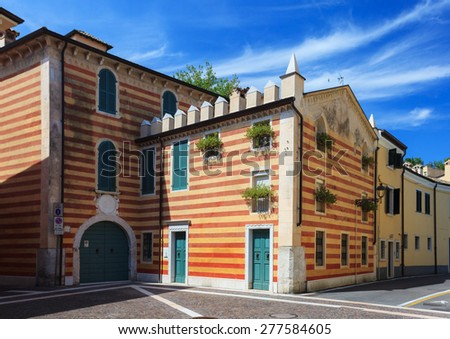 Striped building in Bardolino, typical style of region Veneto in Italy