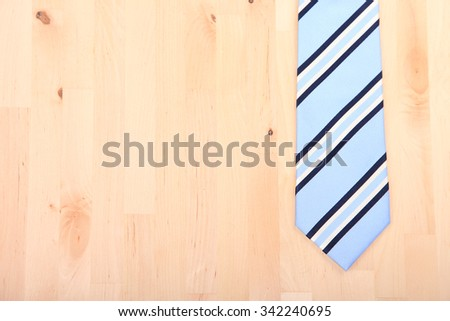 Striped business tie on wooden background - stock photo