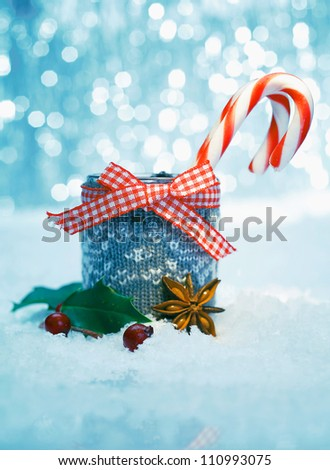 Striped Christmas candy in a rustic container with a checked red and white bow standing in falling snow - stock photo