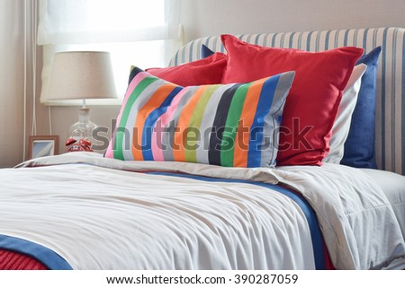 striped headboard with colorful pillows and striped pillow on white bed sheet - stock photo