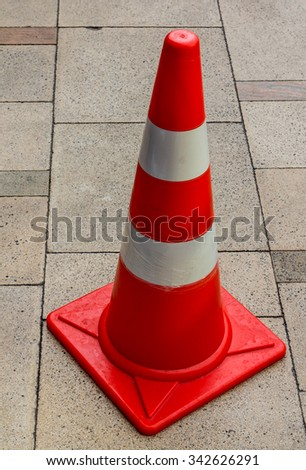 striped orange cones stand on gray asphalt road - stock photo