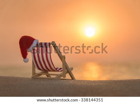 Striped red-white deckchair with christmas santa hat at ocean sandy beach during sunset, xmas or New Year's vacation in hot countries concept - stock photo