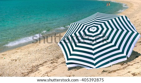 striped sunshade on a beach in Corsica at the turquoise blue sea - stock photo