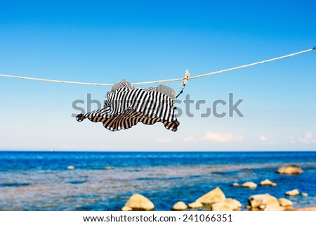 Striped top hanging on a rope on the beach - stock photo