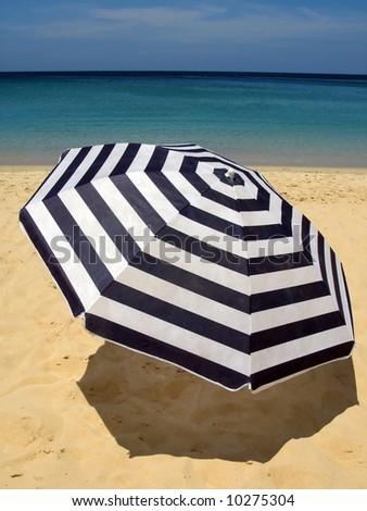 Striped umbrella against sandy beach and ocean - stock photo