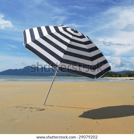 Striped umbrella on a sandy beach of Langkawi island - stock photo