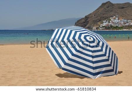 Striped umbrella on the Teresitas beach of Tenerife island. Canaries - stock photo
