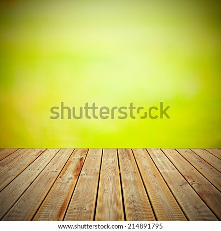 Striped wooden plank deck with the view to abstract bokeh of green foliage background - stock photo