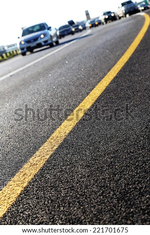 Stripes on highway exit ramp with vehicles in the background - stock photo