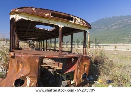 stripped rusty, old abandoned bus wreck in arid mountainous landscape of Montenegro