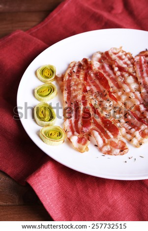 Strips of bacon with slices shallot in white plate with napkin on wooden table background - stock photo