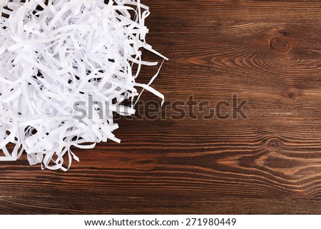 Strips of destroyed paper from shredder on wooden background - stock photo