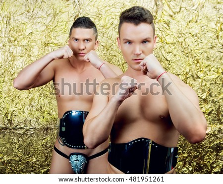 striptease dancers wearing costumes  in the studio isolated against golden studio background
