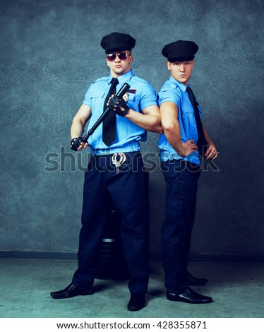 striptease dancers wearing costumes of policemen in the studio - stock photo