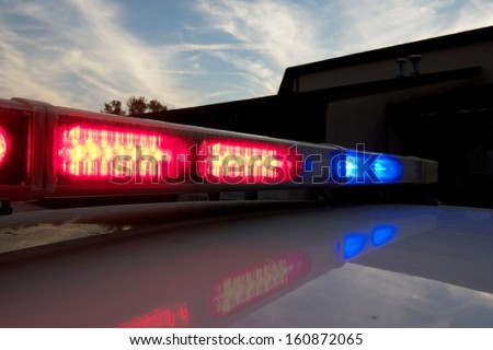 Strobelight bar on top of police car flashing red and blue. - stock photo