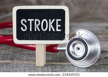 Stroke and stethoscope. Medecine concept. Blackboard with word stroke and stethoscope - stock photo