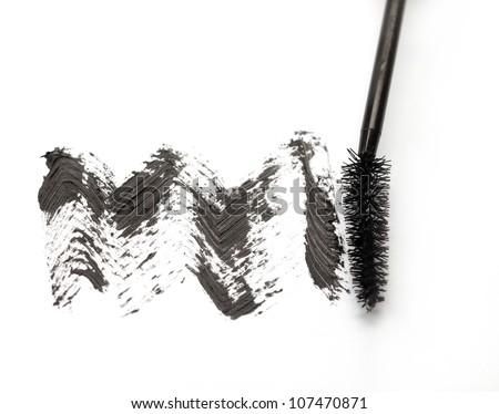 Stroke of black mascara with applicator brush on white background - stock photo