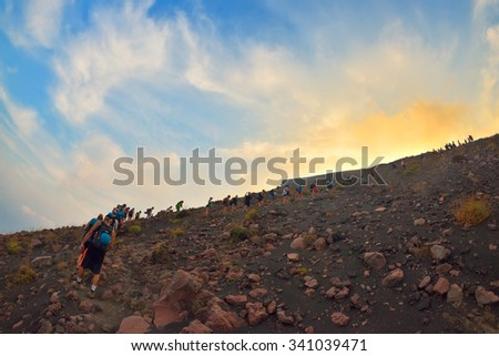STROMBOLI VOLCANO, ITALY - AUGUST 2015: Group of tourists hiking on top of the Stromboli Volcano in the Aeolian Islands, Sicily, Italy, August, 2015 - stock photo