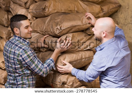 Strong adult workmen unloading shed with coal bags 