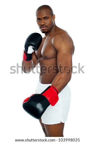 Strong african male boxer wearing black boxing gloves looking at you