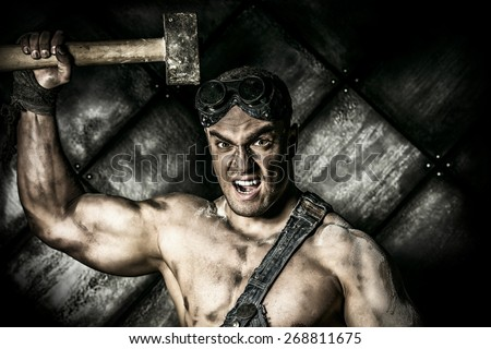 Strong aggressive coal miner with a hammer over dark grunge background. Mining industry. Art concept. - stock photo