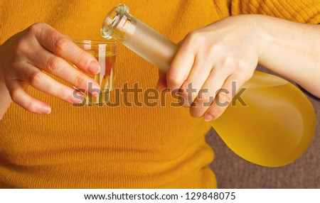 Strong alcohol, pour from a bottle - stock photo