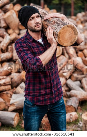Strong and confident. Serious young forester carrying huge log on his shoulder and looking away while standing outdoors - stock photo