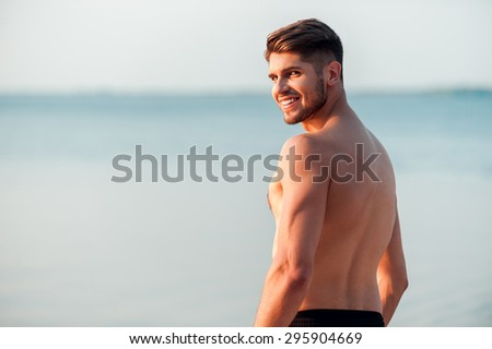 Strong and handsome. Rear view of young muscular man looking over shoulder and smiling while standing at the seaside - stock photo