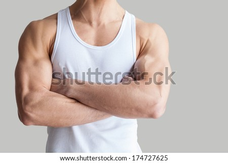 Strong and healthy body. Cropped image of muscular man keeping arms crossed while standing isolated on grey background - stock photo