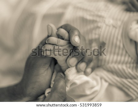 Strong and loving fathers hand holding his infant daughters hand