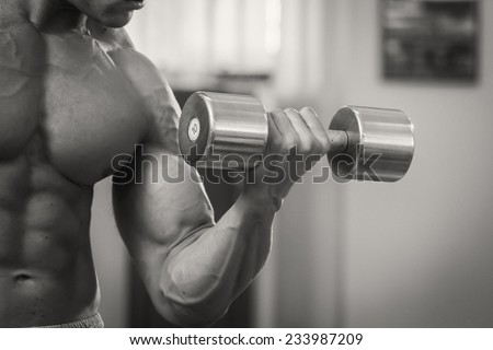 Strong and muscular guy with dumbbell. Handsome muscular man working out with dumbbells in gym.Sport, power, dumbbells, tension, exercise - the concept of a healthy lifestyle. - stock photo