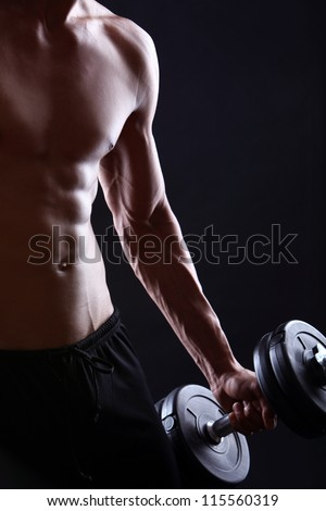 Strong and muscular guy with dumbbell over black background - stock photo