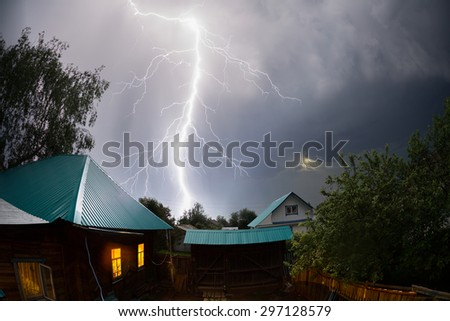 Strong and powerful thunderbolt over houses in the village at night - stock photo