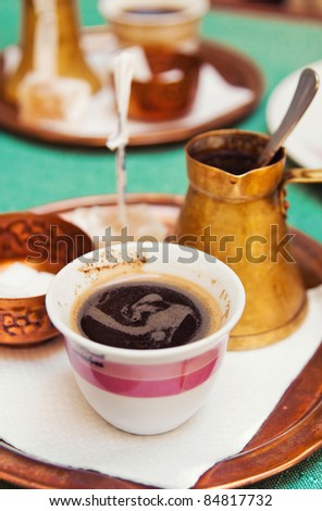 Strong arabic coffee served in a traditional way (shallow dof) - stock photo