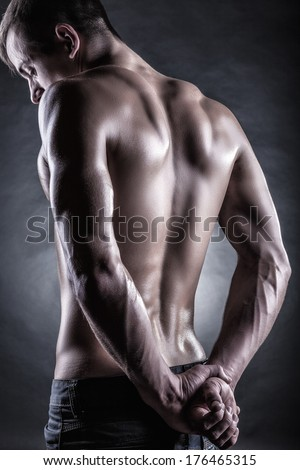 Strong athletic man back on dark background - stock photo