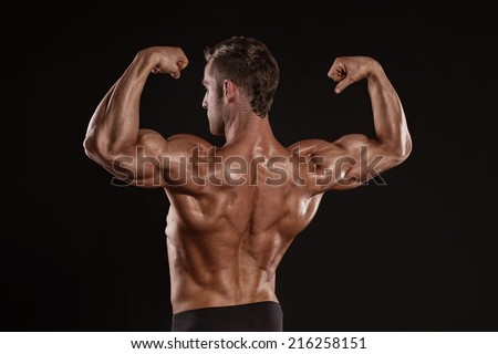 Strong Athletic Man Fitness Model posing back muscles, triceps, latissimus over black background - stock photo
