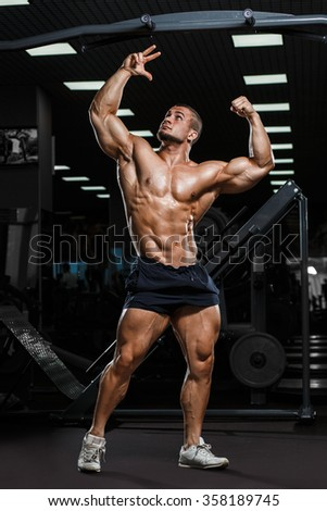 Strong Athletic Man Fitness Model Torso showing muscles in gym - stock photo