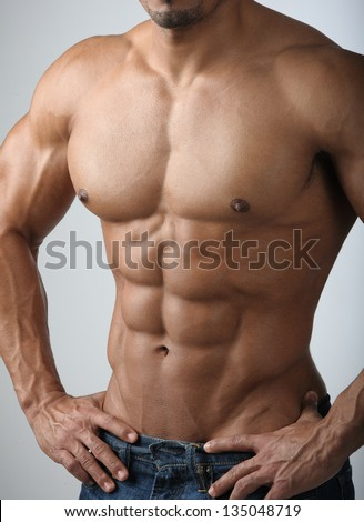 Strong Athletic Man Fitness Model Torso showing six pack abs.  Bodybuilder physique in jeans. - stock photo