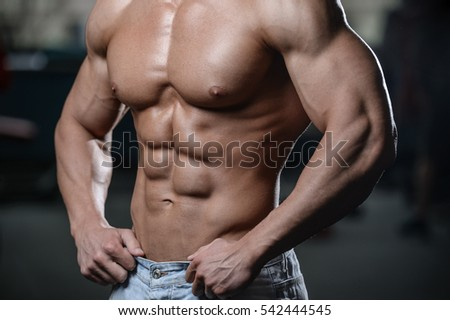 strong athletic man fitness model torso showing six pack abs close up strong abs guy showing in the gym muscles