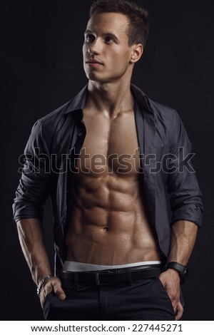 Strong Athletic Man Fitness Model Torso showing six pack abs. isolated on black background - stock photo
