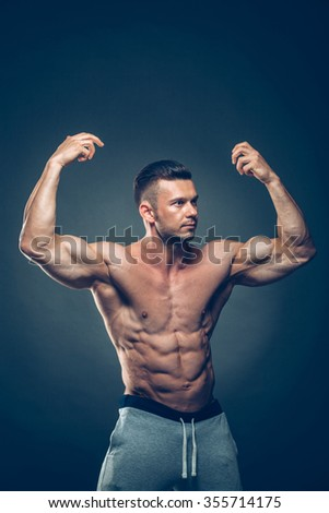 Strong Athletic Man Fitness Model Torso showing six pack abs. isolated on black background with copyspace. - stock photo