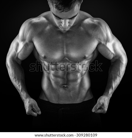 Strong athletic man fitness model torso showing six pack abs, perfect abs, shoulders, biceps, triceps and chest. Black and white photo - stock photo