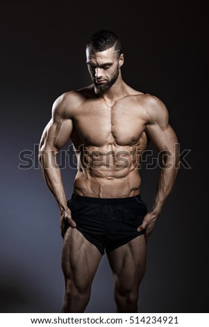 Strong Athletic Man Fitness Model Torso showing six pack abs.  Young sexy bodybuilder with perfect body. Guy with muscle cubes on press. Sport concept image